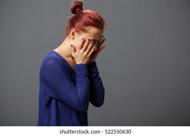 Young suffering from headache woman closing the face with the palms, gray background