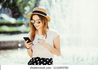 Young summer beauty woman with phone chating or surf in internet drinks mojito fruit cocktail against fountain in the street