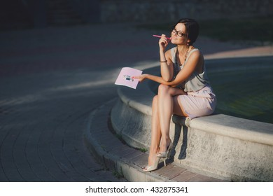 young sun burnt lady with a notebook. summer evening sunset