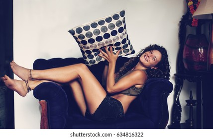 Young sunburned curly woman throwing a pillow and smile to the camera