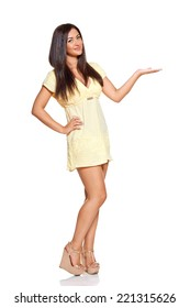 young sun-tanned woman  dressed in a lite summer yellow dress  showing open palm presenting something, isolated on white background