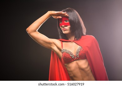 Young super hero woman looking in distance and ready to help her society that is in danger isolated on black background in studio.