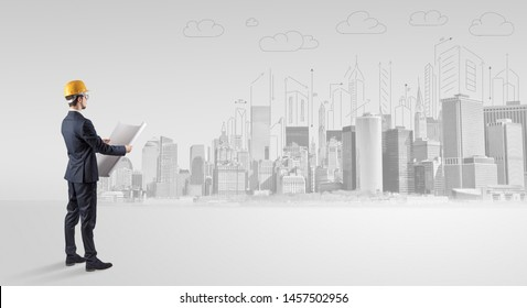 Young supervisor architect standing and replanning a big city panorama
