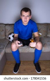 young supporter in uniform sitting on the sofa and watching football with beer and chips
