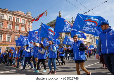 """Young supporters of the political party """"United Russia"""" are walking along the city streets with party flags in their hands on May 1, 2017 in St. Petersburg, Russia"""