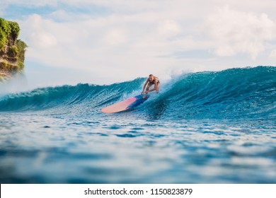 Young surf woman with surfboard on wave. Surfer and ocean wave
