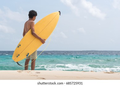 Young surfer carrying his surfboard on a beach