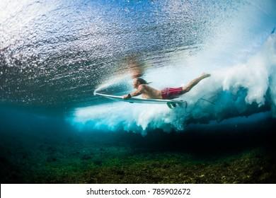 Jovem surfista mergulha sob a onda do oceano com prancha de surf e executa truque chamado no surf como um mergulho de pato