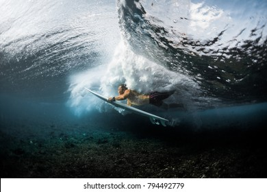 Young surfer dives under the ocean wave with surfboard. Performs trick named Duck Dive to pass the wave