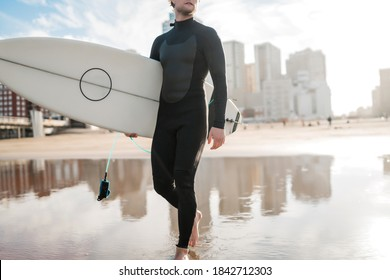 Young surfer entering into the water with his surfboard in a black surfing suit. Sport and water sport concept.