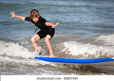 Young surfer girl is riding a wave.