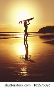 young surfer girl with surfboard at sunrise