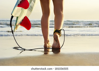 young surfer girl walking to the surf with her board