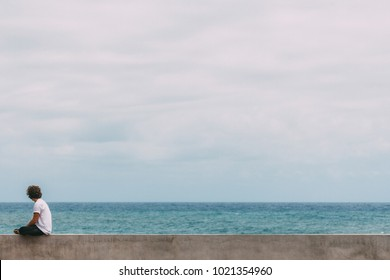 Young surfer sitting on a concrete wall with long brown curly hair in white t-shirt is watching the blue ocean and searching for waves