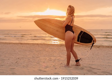 Young surfer woman with sporty body posing on beach at warm sunset or sunrise. Attractive surfgirl with surfboard