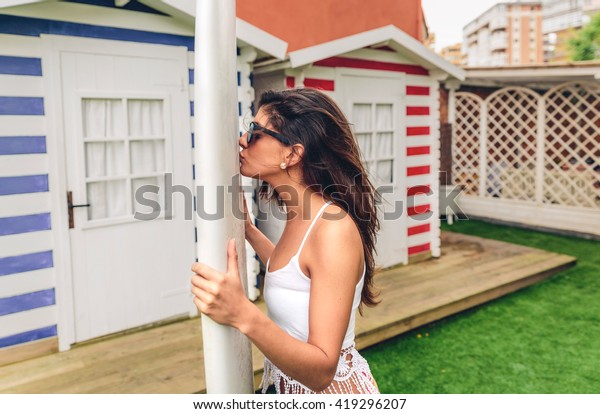 Young surfer woman with top and bikini kissing surfboard