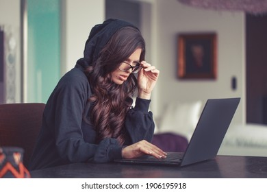 Young surpised Caucasian woman in hoodie seeing unbelievable thing on internet, taking down glasses