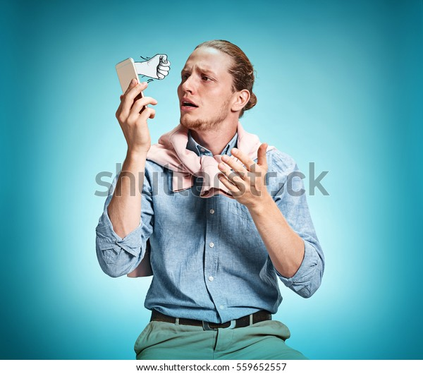 The young surprised caucasian businessman on blue background talking by cell phone