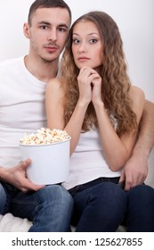 young surprised couple sitting on the sofa eating popcorn and watching  tv