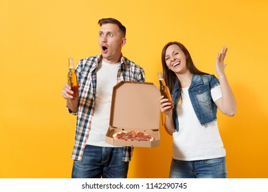 Young surprised couple woman man sport fans cheer up support team holding beer bottle italian pizza in cardboard flatbox spreading hands isolated on yellow background. Sport family leisure lifestyle