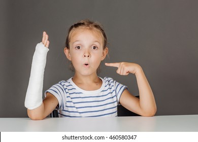 Young surprised girl with broken arm is sitting at the table. she is pointing at her broken arm.