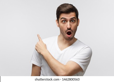 Young surprised man isolated on gray background in white t-shirt looking at camera with open mouth, pointing left, copyspace for ads