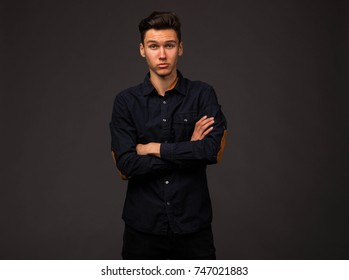 Young surprised man portrait of a confident businessman on a black background. Ideal for banners, registration forms, presentation, landings, presenting concept.