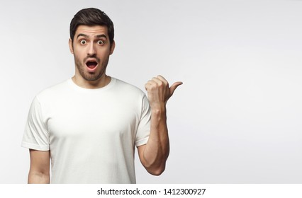 Young surprised man in white t-shirt looking at camera with open mouth, pointing right, copy space for ads, isolated on gray background