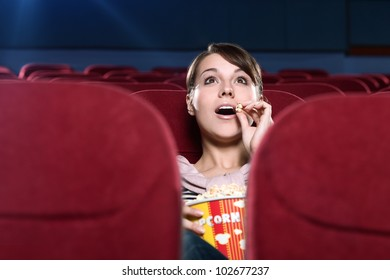 Young surprised woman eating popcorn in the movie theater
