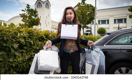 Young surprised woman holds many shopping bags in tooth and hands. Pensive girl with a lot of purchases after a shopping day in Outlet Village. Confused female person standing on parking near a stores
