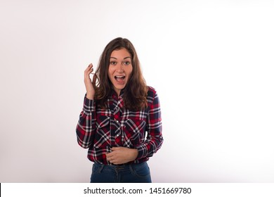 Young surprised woman with open mouth standing isolated in studio against wall background for promotional content. Shocked hipster girl in stylish shirt looking in camera