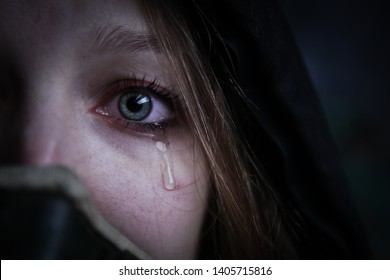 Young survivalist crying woman in gas mask with red eyes and tears on her face looking into camera close up portrait
