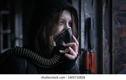 Young survivalist crying woman in gas mask with tears on her face looking in front of her with ak rifle on the background with apocalyptic war area around
