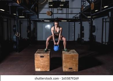 Junge, schwitzige, muskulöse Mädchen mit großen Muskeln und starken Beinen, die tief schwamm und tauchen auf zwei hölzernen Sprungkästen mit schweren Kettlebell für Hardcore Cross-Kraft Training im Fitnessraum