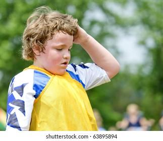 Young sweaty soccer boy wiping wet hair