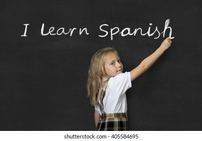 young sweet junior schoolgirl with blonde hair standing happy writing with chalk on class blackboard I learn Spanish text in children learning language and education concept