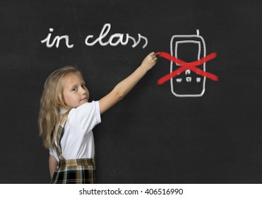 young sweet junior schoolgirl with blonde hair standing happy and smiling writing with chalk about not using mobile phone in school class in education rules and cellular forbidden concept
