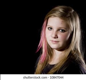 Young, sweet  teenage girl posing on black background