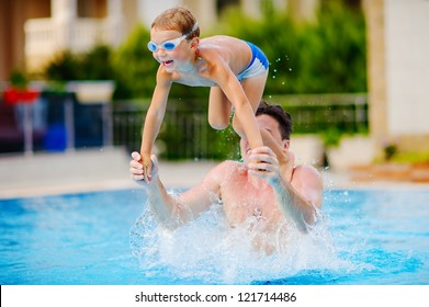 young swimmer boy on swim start at swimming pool ready for jump race and win. Father teach her son to swim.