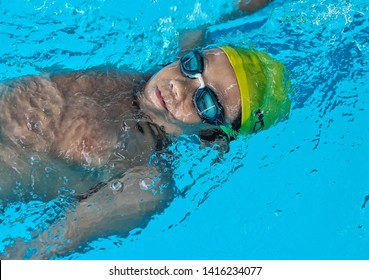 Young swimmer swimming Backstroke in the deep swimming pool