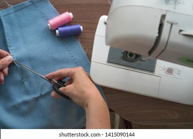 A young tailor, a seamstress, cuts the threads in the basting seam of the dye of the cut skirt. Nearby is a sewing machine on a brown table. Work in a sewing studio