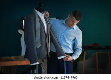 Young tailor taking measurements of jacket on mannequin in atelier