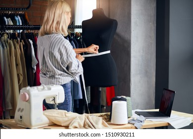 young tailor working with measuring tape, dressmaker measuring the belly od dummy, close up photo