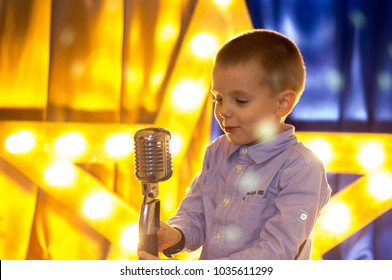 Young talent boy singing with retro microphone on the illuminated stage