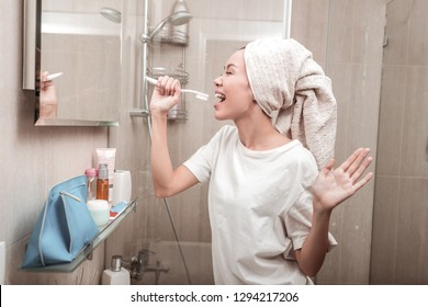 Young talent. Nice Asian woman singing into the toothbrush while pretending to be a singer