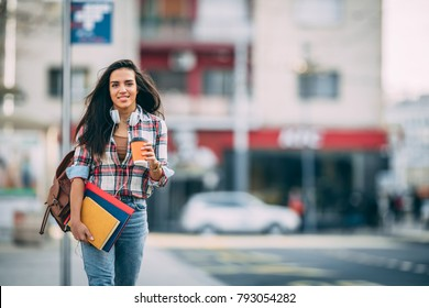 Young talented female student dressed in casual clothing walking around city and listening to favorite radio station via earphones. Attractive brunette woman enjoying free time outdoors with music.