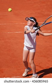 Young talented girl hits a volley on the tennis court