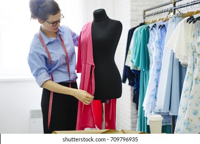 Young talented seamstress wearing pink dress on mannequin to making measurements standing in own stylish atelier studio.Female couturier in eyeglasses and tape working on design of new garment