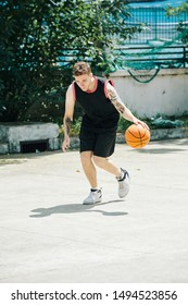 Young tall Caucasian man in black sports uniform playing backetball court outdoors
