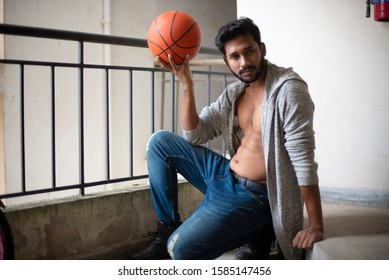An young tall, dark and handsome Indian Bengali man in a front open western jacket and jeans playing with basket ball in a balcony in white background. Indian lifestyle and fashion.